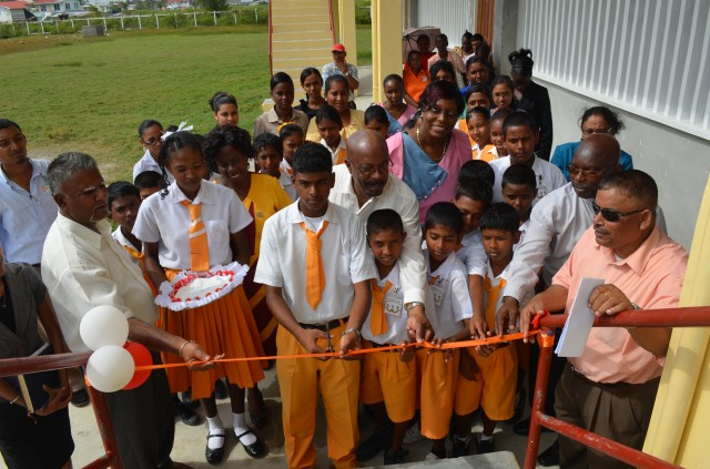 Minister of Local Government and Regional Development Norman Whittaker assists students of the Woodley Park Secondary School to commission the new department