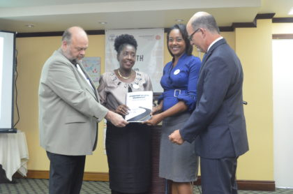 US Ambassador to Guyana Perry Holloway, Minister within the Ministry of Communities Valarie Adams-Patterson, Ministry of Social Cohesion representative and YCP project representative pose with a copy of the manual which was created from the project.
