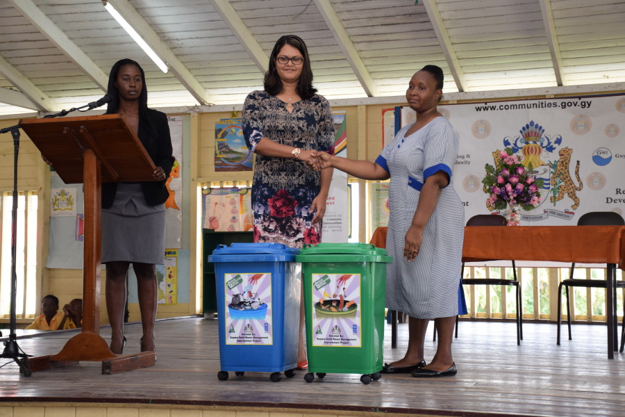 Coordinator of the Community Infrastructure Improvement Project (CIIP), Karen Roopchand, ceremonially handing over two of the waste receptacles to Headmistress of the West Ruimveldt Primary School, Anika Osborne