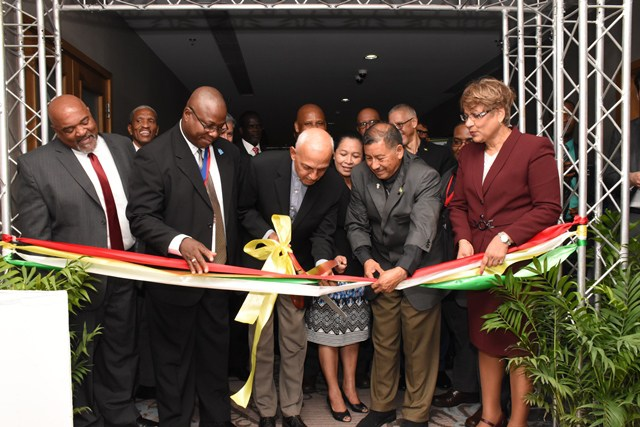 Minister of Communities, Ronald Bulkan cutting the ribbon to open the 26th Caribbean Water and Wastewater Association (CWWA) being assisted by Vice President and Ministry of Indigenous Peoples Affairs, Sydney Allicock and President, CWWA, Alphonsus Daniel and other Minsters and representatives from other members of CWWA