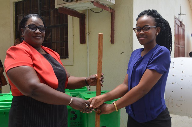 [from right to left] Russhell Parris, Sanitation Management staff hands over agriculture equipment and waste receptacles to Cindy Cooper-Crandon, Headteacher, Ann's Grove Secondary School.