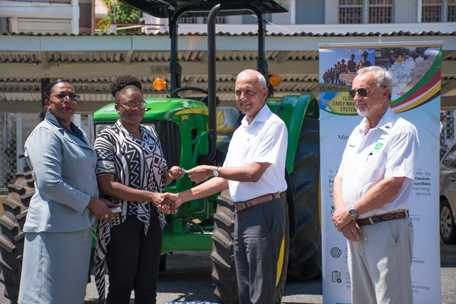 Minister of Communities, Ronald Bulkan hands over the tractor keys to Councillor of Linden Town Council, Orleena Obermuller.