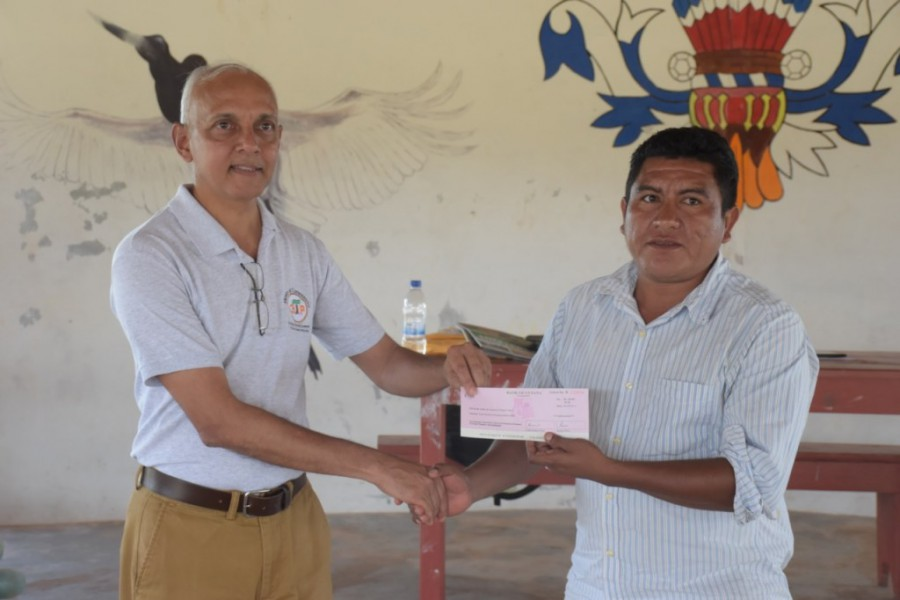 Pleasant problem: Rupertee Senior Councillor, Suresh Andries receives the $800,000 Presidential Grant cheque from Minister of Communities, Ronald Bulkan during the massive Ministerial Outreach in the Rupununi Region