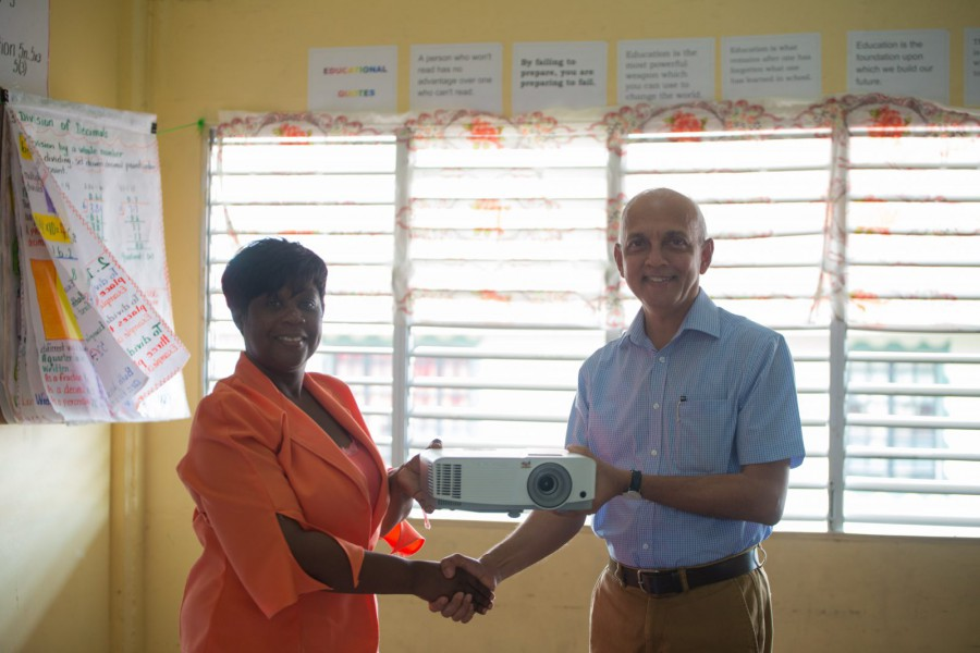 Minister of Communities Ronald Bulkan presents a multimedia projector to Headteacher of Sophia Primary School Audrey Sue